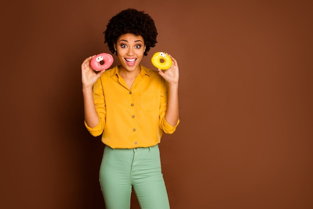 Zdjęcie śmiesznej ładnej ciemnej skóry kręconej pani trzymającej dwa kolorowe pączki o karmelowych oczach ludzkie twarze dobry nastrój nosić żółtą koszulę zielone spodnie na białym tle brązowy kolor