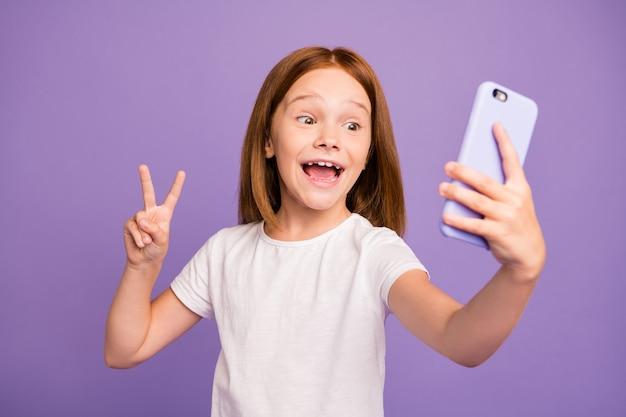 Zdjęcie śmiesznej małej damy trzymającej telefon robiąc selfie pokazujący znak v