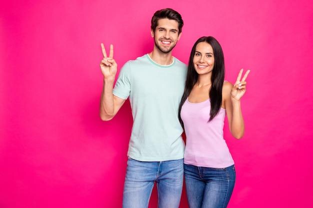 Zdjęcie śmiesznej pary faceta i pani podnoszących ręce pokazujących symbole v-znak, mówiąc `` cześć '' i `` do widzenia '', nosić ubranie na białym tle jasny różowy kolor tła