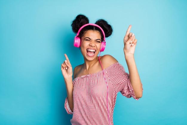 Zdjęcie śmiesznej szalonej ciemnoskórej pani słuchaj muzyki nowoczesne słuchawki śpiewają ulubioną piosenkę podnieś palce tańcz nosić modną czerwoną białą koszulę w paski z odkrytymi ramionami izolowany niebieski kolor ściana