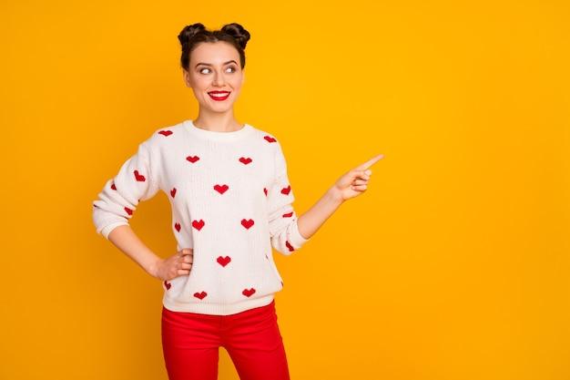 Zdjęcie śmiesznej wesołej pani pokaż wyprzedaż niskie ceny wskazują palec pustą przestrzeń nowy baner reklamowy nosić biały sweter w serduszka