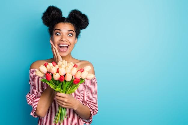 Zdjęcie śmiesznej zszokowanej ciemnej skóry pani trzyma duży bukiet tulipanów, otwarte usta dłoń na policzku nosić paski czerwoną białą bluzkę z odkrytymi ramionami izolowana niebieska ściana