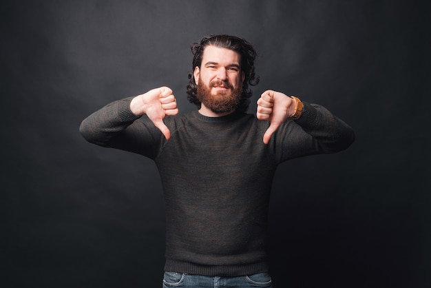 Zdjęcie smutny brodaty mężczyzna pokazuje kciuk w dół w ciemności