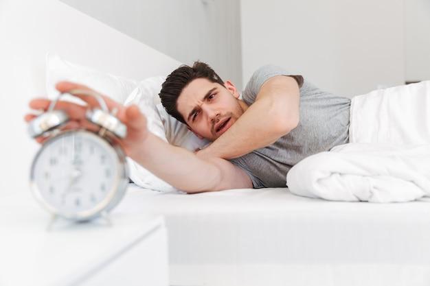 Zdjęcie śpiącego brunetki w przypadkowych ubraniach wyłącza alarm, a budzi się rano