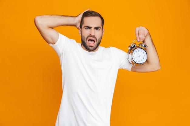 Zdjęcie spiętego mężczyzny 30s w codziennym noszeniu, trzymając budzik, na białym tle