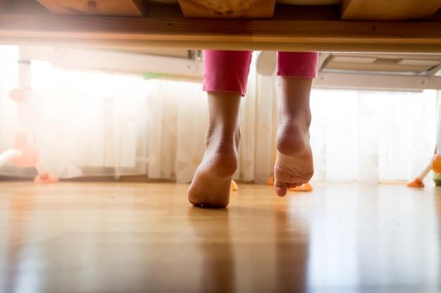 Zdjęcie spod łóżka dziewczyny wchodzącej na drewnianą podłogę w sypialni