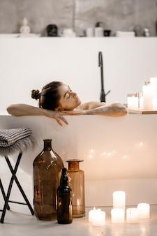 Zdjęcie spokojnej i uroczej kobiety spędzającej wolny czas w wodzie z pianką i świecami w mieszkaniu