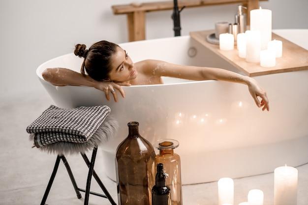 Zdjęcie spokojnej i uroczej kobiety wypoczywającej w wodzie z pianą i świecami w mieszkaniu, zdrowym leczeniu i przyjemności.