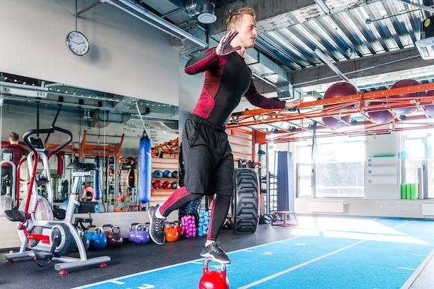 Zdjęcie sportowca utrzymuje równowagę stojąc z jedną nogą na wadze