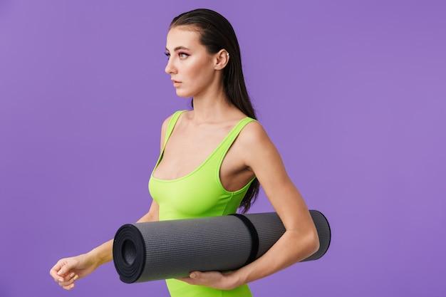 Zdjęcie sportowej poważnej kobiety z jasnym makijażem, trzymającej matę do jogi i patrzącą w przyszłość