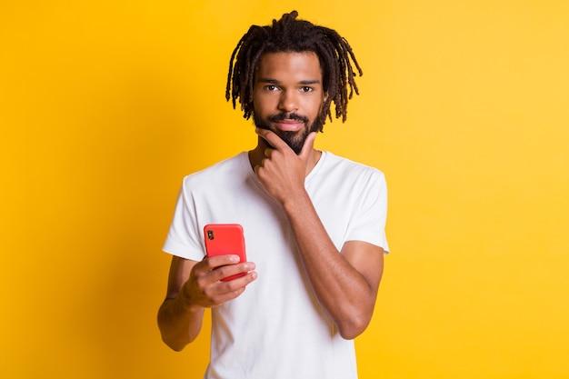Zdjęcie sprytnego studenta ciemnoskórego faceta trzymającego telefon za rękę na brodzie ma fajny pomysł nosić koszulkę na białym tle żółty kolor tła