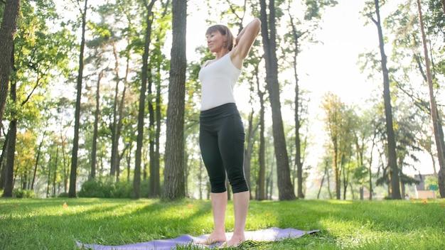 Zdjęcie średniej wieku uśmiechnięta kobieta praktykuje jogę i medytuje w parku. kobieta rozciągająca się i ćwicząca fitness na macie w lesie