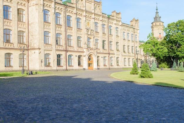 Zdjęcie starego budynku uniwersyteckiego z zielonym parkiem o wschodzie słońca