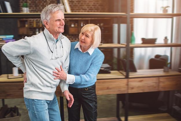 Zdjęcie starego człowieka trzymającego rękę na plecach. boli go