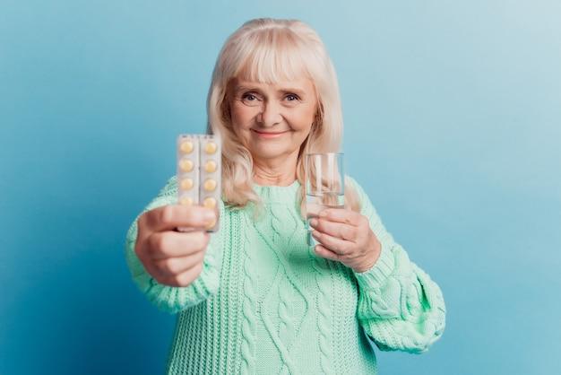 Zdjęcie starej kobiety daje pigułkom szklankę wody na białym tle na niebieskim tle