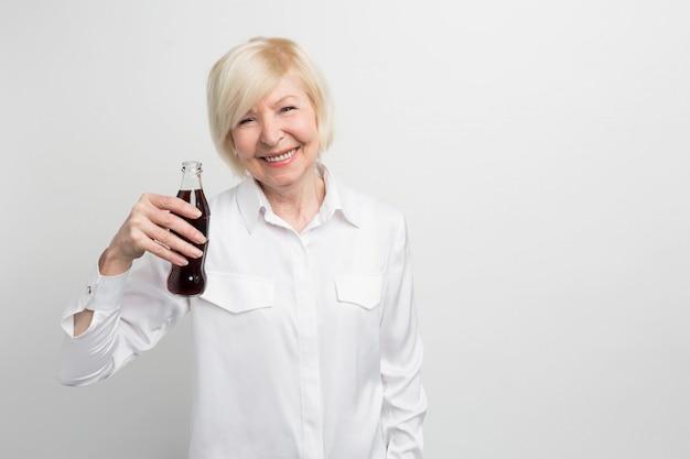 Zdjęcie starej kobiety degustującej coca-colę. lubi ten napój od dzieciństwa. to nie jest zdrowy napój, ale ona to lubi.