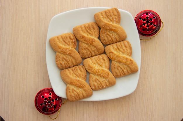 Zdjęcie stosu ciasteczek lub ciasteczek kruche na talerzu z czerwonymi dzwoneczkami. tło narodowego dnia ciasteczek. świąteczne śniadanie dla mikołaja.