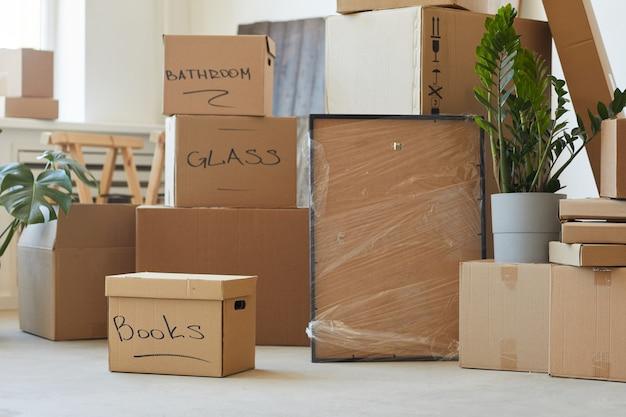 Zdjęcie stosu podpisanych kartonów w pomieszczeniu przygotowanym do przeprowadzki