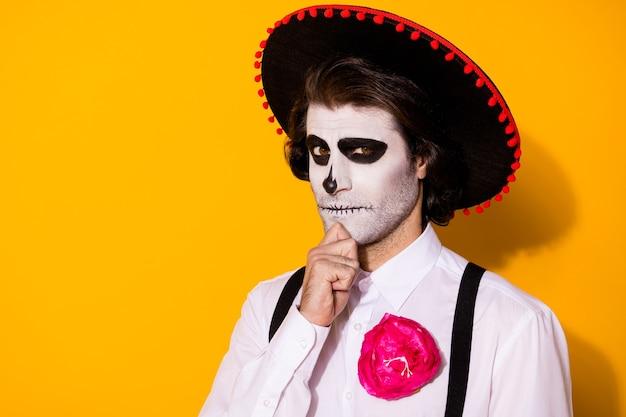 Zdjęcie straszny podstępny zły duch facet ręka podbródek zastanawiam się chcę stworzyć wehikuł czasu powrót życie nosić biała koszula kwiat śmierć kostium cukier czaszka szelki na białym tle żółty kolor tło