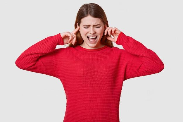 Zdjęcie stresującej ciemnowłosej kobiety w czerwonym swetrze, paniki, niczego nie chce słyszeć, jest zdesperowana