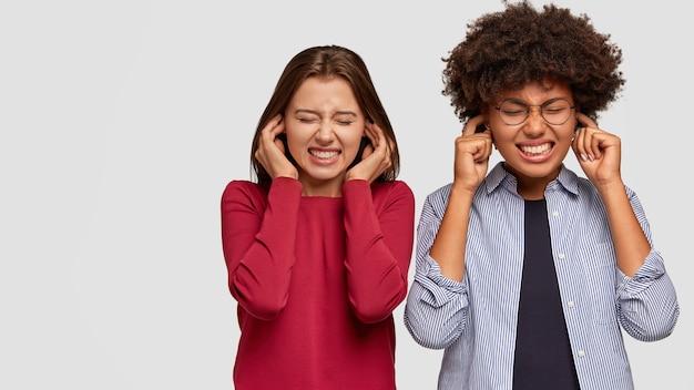 Zdjęcie stresujących dziewczyn zaciskających zęby, zatykających uszy, ignorujących nieprzyjemne dźwięki, stojących blisko, ubranych w swobodny strój, odizolowanych na białej ścianie z wolnym miejscem na reklamę lub promocję