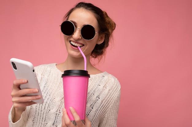 Zdjęcie strzał atrakcyjnej młodej szczęśliwej uśmiechniętej brunetki ubranej w biały sweter i kolorowe
