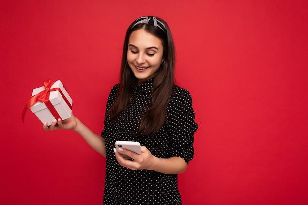 Zdjęcie strzał atrakcyjny ładny pozytywny uśmiechnięta brunetka dziewczyna na białym tle nad czerwonym tle ściany ubrana w czarną bluzkę trzymając białe pudełko z czerwoną wstążką i patrząc na ekran telefonu komórkowego.