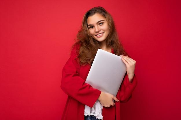 Zdjęcie strzał piękne uśmiechnięta szczęśliwa młoda brunet kobieta trzyma blisko komputera laptop na sobie czerwony sweter i białą bluzkę patrząc na kamery na białym tle na czerwonym tle.