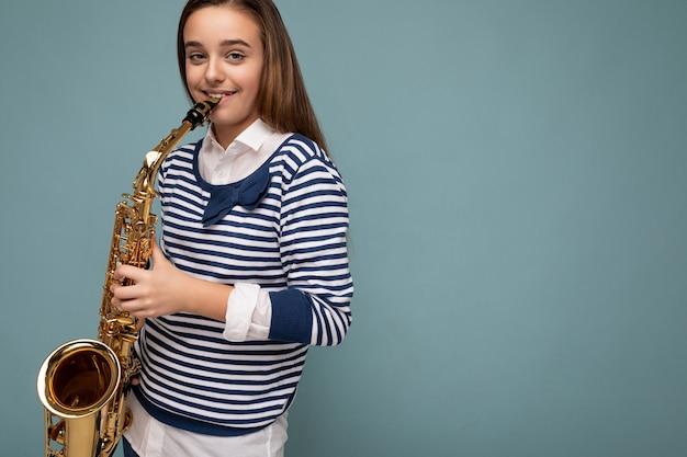 Zdjęcie strzał pięknej szczęśliwej uśmiechniętej brunetki małej dziewczynki ubrana w pasiasty długi rękaw stojący