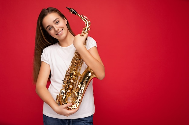 Zdjęcie strzał pięknej szczęśliwej uśmiechniętej brunetki małej dziewczynki ubranej w białą koszulkę dla makiety stojącej