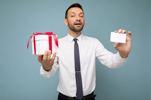 Zdjęcie strzał przystojny szczęśliwy biznesmen młody nieogolony brunetka z brodą na białym tle nad niebieskim