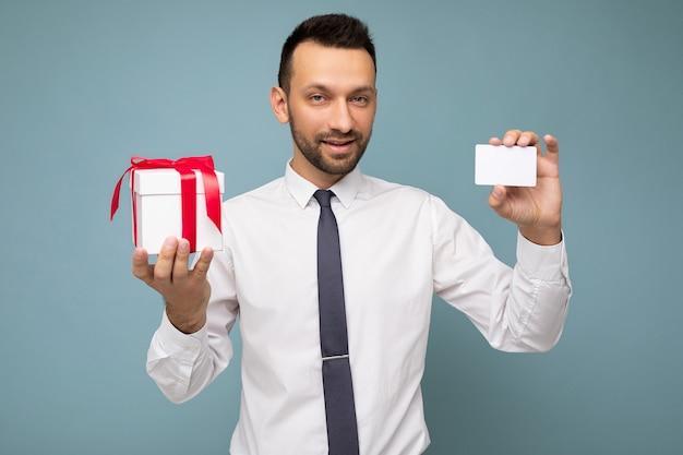 Zdjęcie strzał przystojny szczęśliwy brunetka młody nieogolony mężczyzna z brodą na białym tle na niebieskim tle