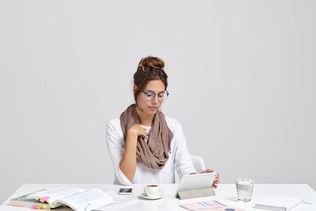 Zdjęcie studenta czyta na tablecie informacje ze strony edukacyjnej