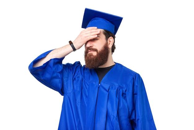 Zdjęcie studenta noszącego kawalera i robiącego facepalm