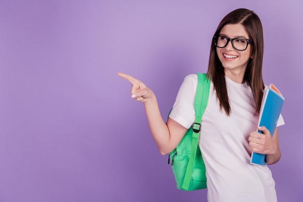 Zdjęcie studentki dziewczyny trzymaj zeszyty worek punkt palec pusta przestrzeń na białym tle fioletowe tło