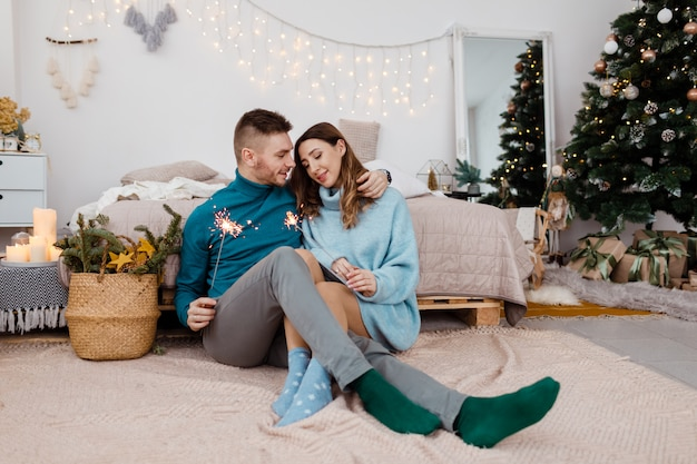 Zdjęcie stylowe kochający mężczyzna i kobieta w ciąży z sparklers