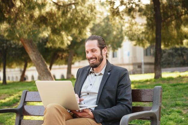 Zdjęcie stylowego dorosłego człowieka z wiązanymi włosami, śmiejąc się podczas pracy na srebrnym laptopie i siedząc na ławce w zielonym parku