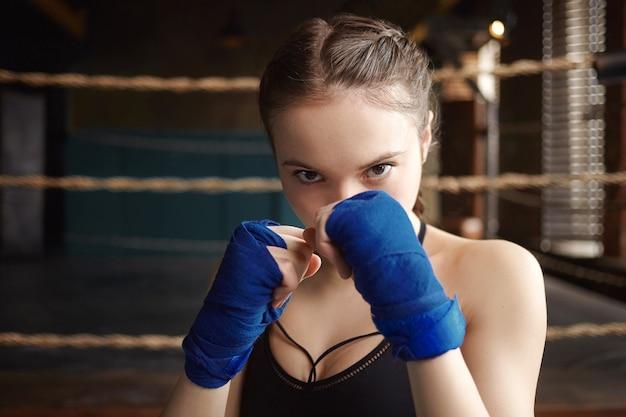 Zdjęcie stylowej 18-letniej bokserki z silnymi ramionami i wysportowanym ciałem, ćwiczącej w pomieszczeniu, doskonalącej umiejętności i techniki uderzania