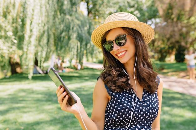 Zdjęcie stylowej kobiety spacerującej po letnim parku w letnim kapeluszu, czarnych okularach przeciwsłonecznych i ślicznej sukience. słucha muzyki i tańczy z ogromnymi emocjami.