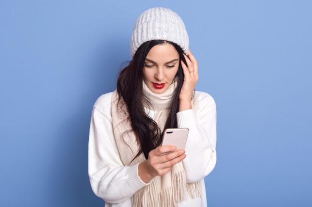 Zdjęcie stylowej ładnej pani patrzy na ekran telefonu, rozmawia z wiadomościami, nosi ciepłą czapkę, szalik, sweter