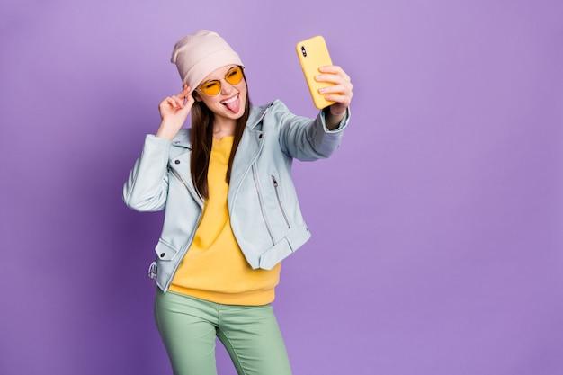 Zdjęcie stylowej ładnej pani trzymaj telefon uśmiechając się pokazując język zrobić selfie zwolennicy bloger nosić okulary przeciwsłoneczne dorywczo kapelusz niebieska kurtka sweter zielony spodnie na białym tle fioletowy kolor tło