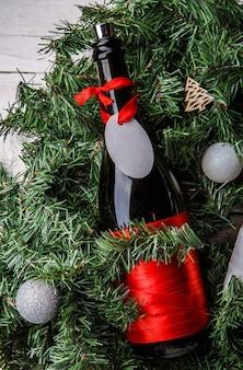Zdjęcie świerkowych gałęzi z butelką wina, pustą kartkę z życzeniami, świąteczne zabawki na białym tle