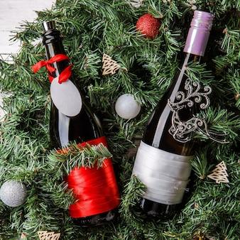 Zdjęcie świerkowych gałęzi z dwiema butelkami wina, pustą kartkę z życzeniami, świąteczne zabawki na białym tle