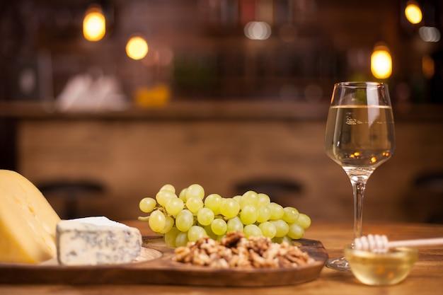 Zdjęcie świeżych winogron obok kieliszek na drewnianym stole. degustacja sera francuskiego. smaczne orzechy włoskie.