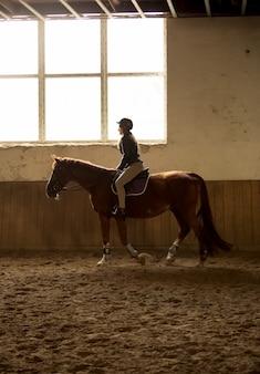 Zdjęcie sylwetki kobiety jadącej na koniu w krytym ujeżdżalni z dużym oknem