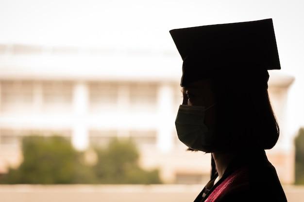 Zdjęcie sylwetki młodej szczęśliwej azjatyckiej absolwentki uniwersytetu w sukni ukończenia szkoły