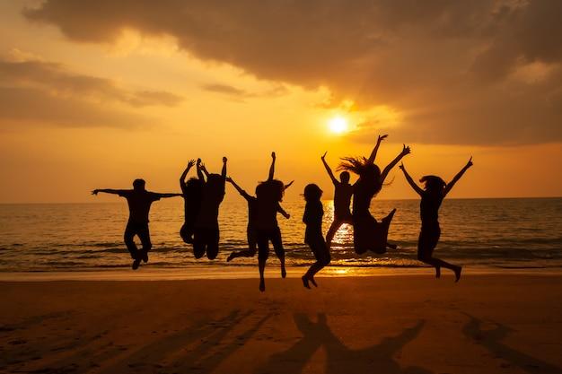 Zdjęcie sylwetki uroczystości zespołu na plaży o zachodzie słońca