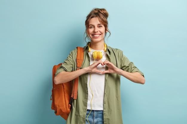 Zdjęcie sympatycznej, ładnej podróżniczki robi gest serca na piersi, wyraża miłość do ludzi, podróżuje tylko z jednym plecakiem