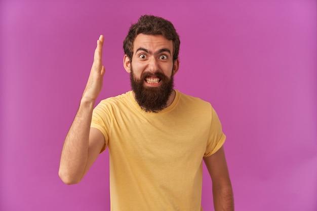 Zdjęcie szalonego brodatego młodego mężczyzny stojącego
