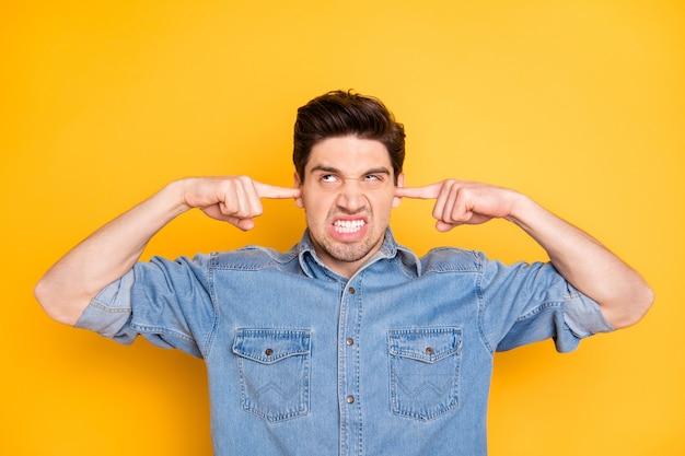 Zdjęcie szalonego szaleńca obłąkanego, że jego górni sąsiedzi hałasują w nocy, zamykając uszy na izolowanej jasnej ścianie